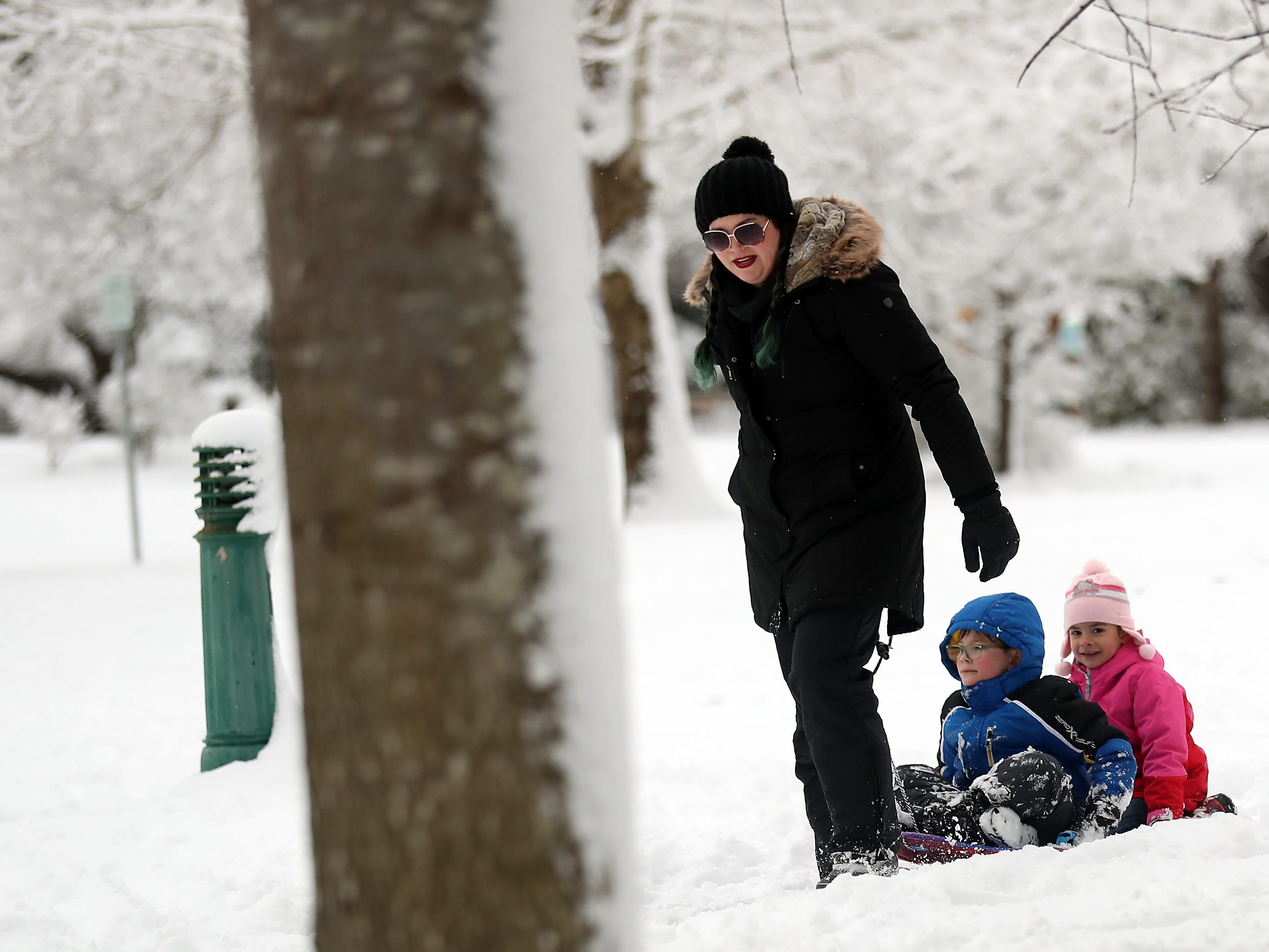Lauren Briggs pulls Arlo Briggs, 6, and Molly Fletcher, 6, through Evergreen Rotary Park on a sled on Saturday, February 9, 2019.