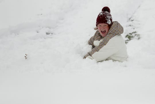 Haylee Arries, 14, laughs as she gets buried in the snow while sledding on a skim board at Evergreen Rotary Park in Bremerton on Saturday, February 9, 2019.