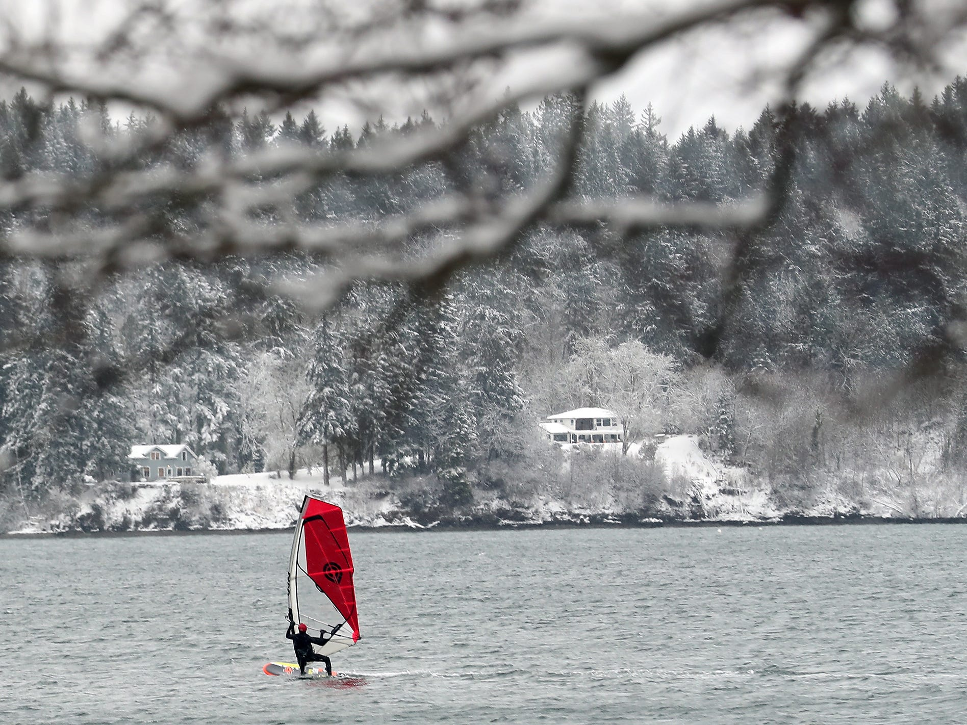A windsurfer braves the snow and cold to ride along Silverdale Waterfront Park on Saturday, February 9, 2019.