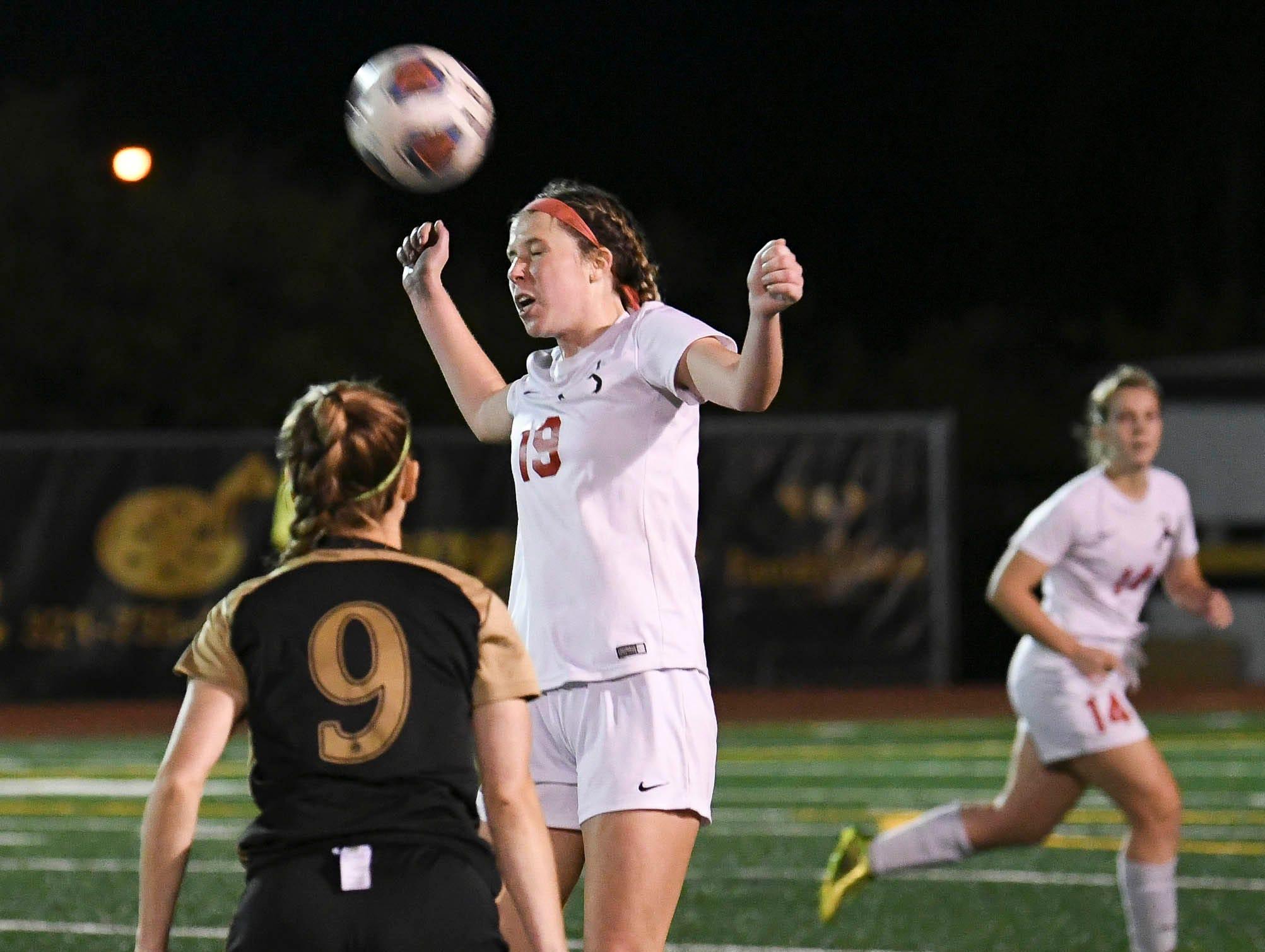Satellite's Abigail Ferguson heads the ball away from Maddie Murphy of Merritt Island during Friday's Class 3A regional semifinal at Merritt Island High