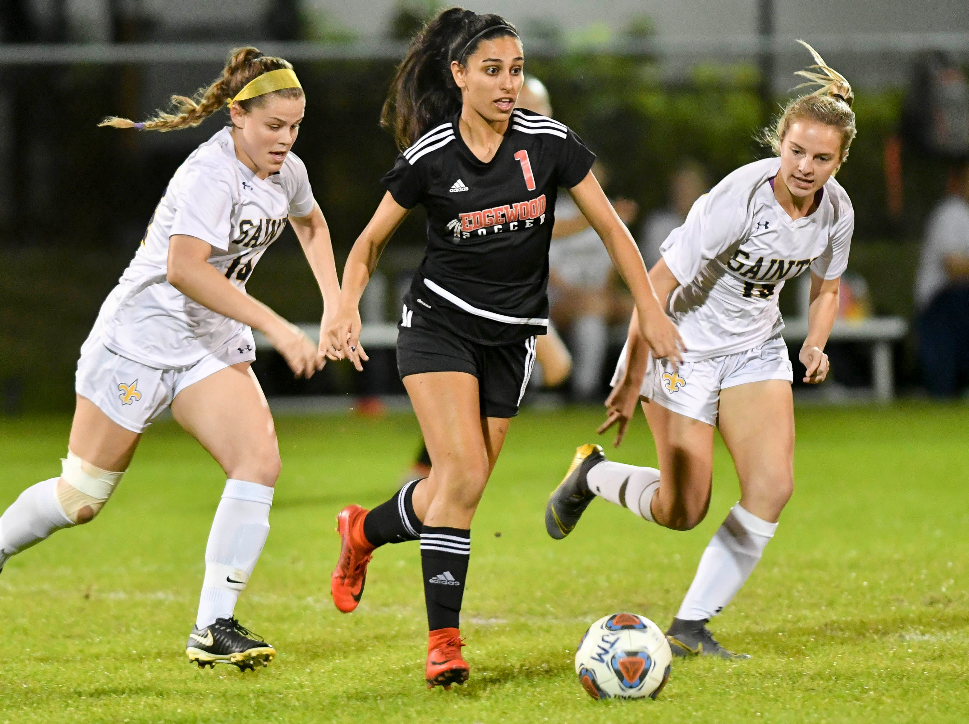 Fran Espinoza of Edgewood (1) is pursued by Meg Parent (14) and Sophia Olore (15) of Trinity Prep during Friday's Class 2A regional semifinal at Edgewood Jr/Sr HIgh