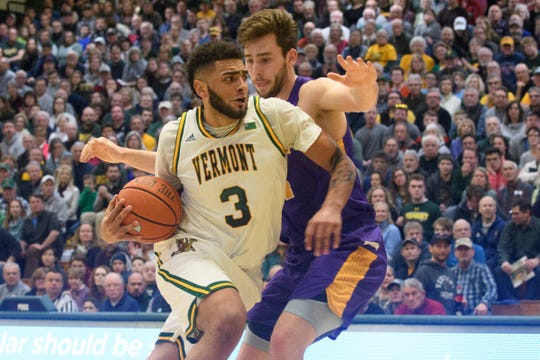 Vermont forward Anthony Lamb (3) drives to the hoop past Albany's Adam Lulka (14) during the men's basketball game between the Albany Great Danes and the Vermont Catamounts at Patrick Gym on Saturday February 9, 2019 in Burlington, Vermont.
