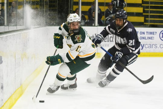 Vermont forward Craig Puffer (17) looks to pass the puck past New Hampshire's Anthony Wyse (21) during the men's hockey game between the New Hampshire Wildcats and the Vermont Catamounts at Gutterson Field House on Friday night February 8, 2019 in Burlington, Vermont. (