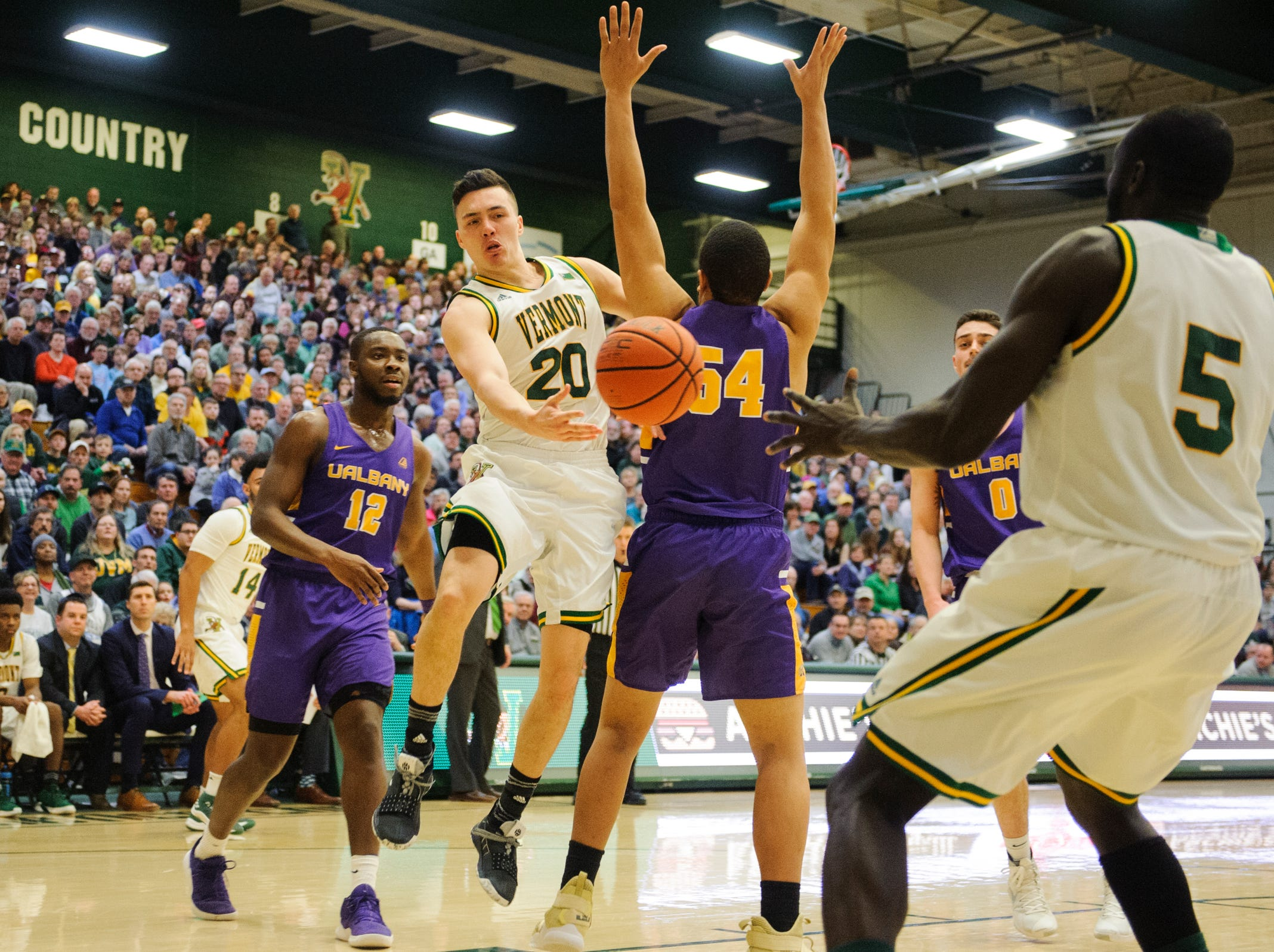 Vermont guard Ernie Duncan (20) passes the ball to Vermont forward Samuel Dingba (5) during the men's basketball game between the Albany Great Danes and the Vermont Catamounts at Patrick Gym on Saturday February 9, 2019 in Burlington, Vermont.