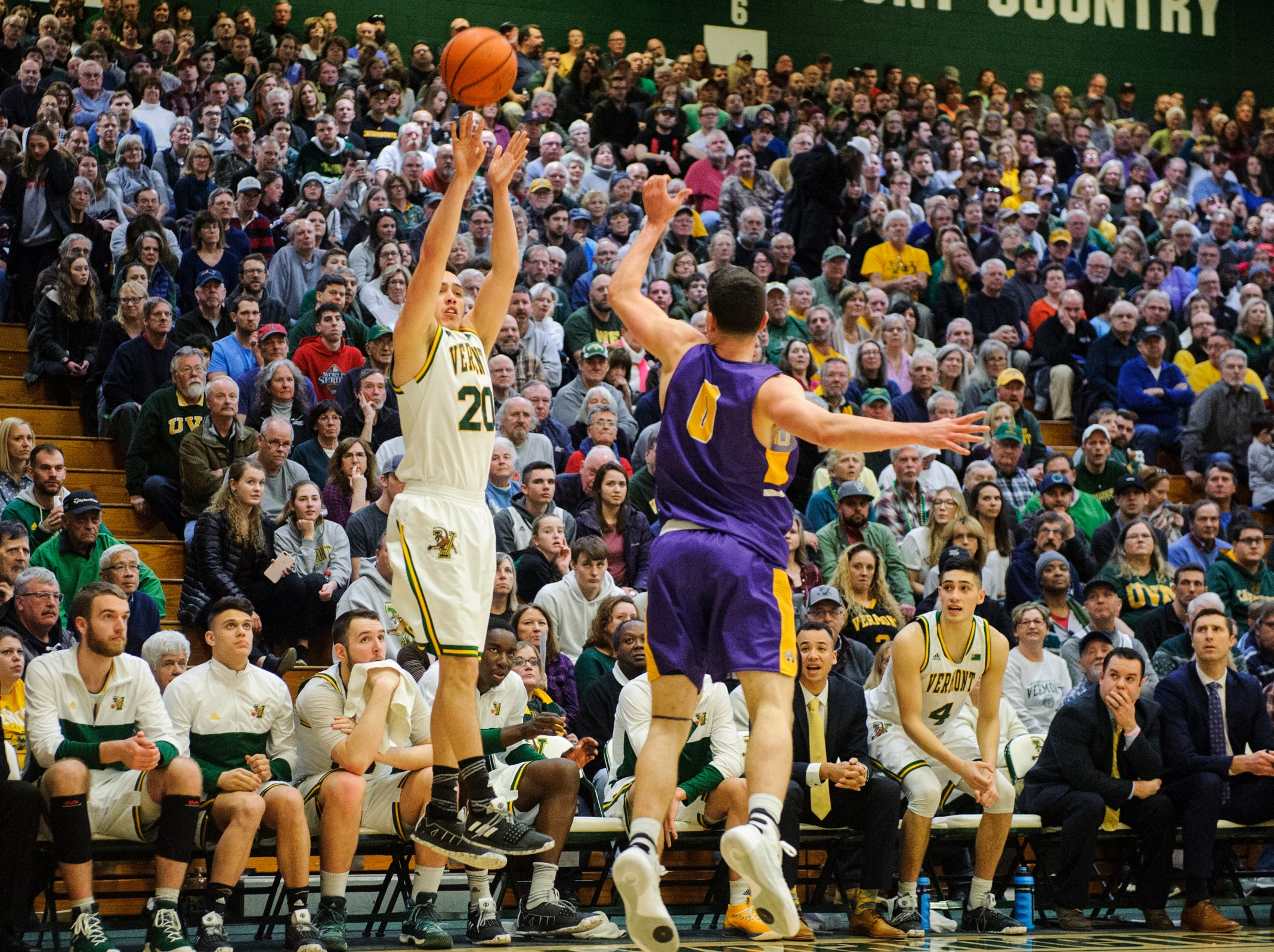 Vermont guard Ernie Duncan (20) shoots a three pointer over Albany's Antonio Rizzuto (0) during the men's basketball game between the Albany Great Danes and the Vermont Catamounts at Patrick Gym on Saturday February 9, 2019 in Burlington, Vermont.