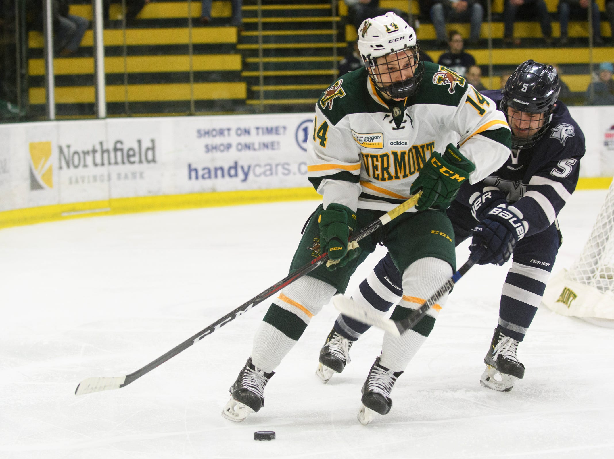Vermont forward Ace Cowans (14) skates with the puck past New Hampshire's Will McKinnon (5) during the men's hockey game between the New Hampshire Wildcats and the Vermont Catamounts at Gutterson Field House on Friday night February 8, 2019 in Burlington, Vermont.