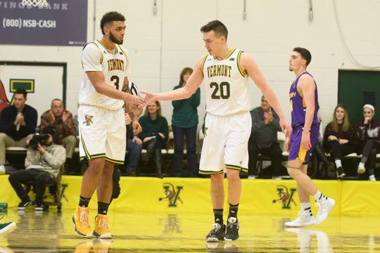 Vermont forward Anthony Lamb (3) and Vermont guard Ernie Duncan (20) high five during the men's basketball game between the Albany Great Danes and the Vermont Catamounts at Patrick Gym on Saturday February 9, 2019 in Burlington, Vermont.