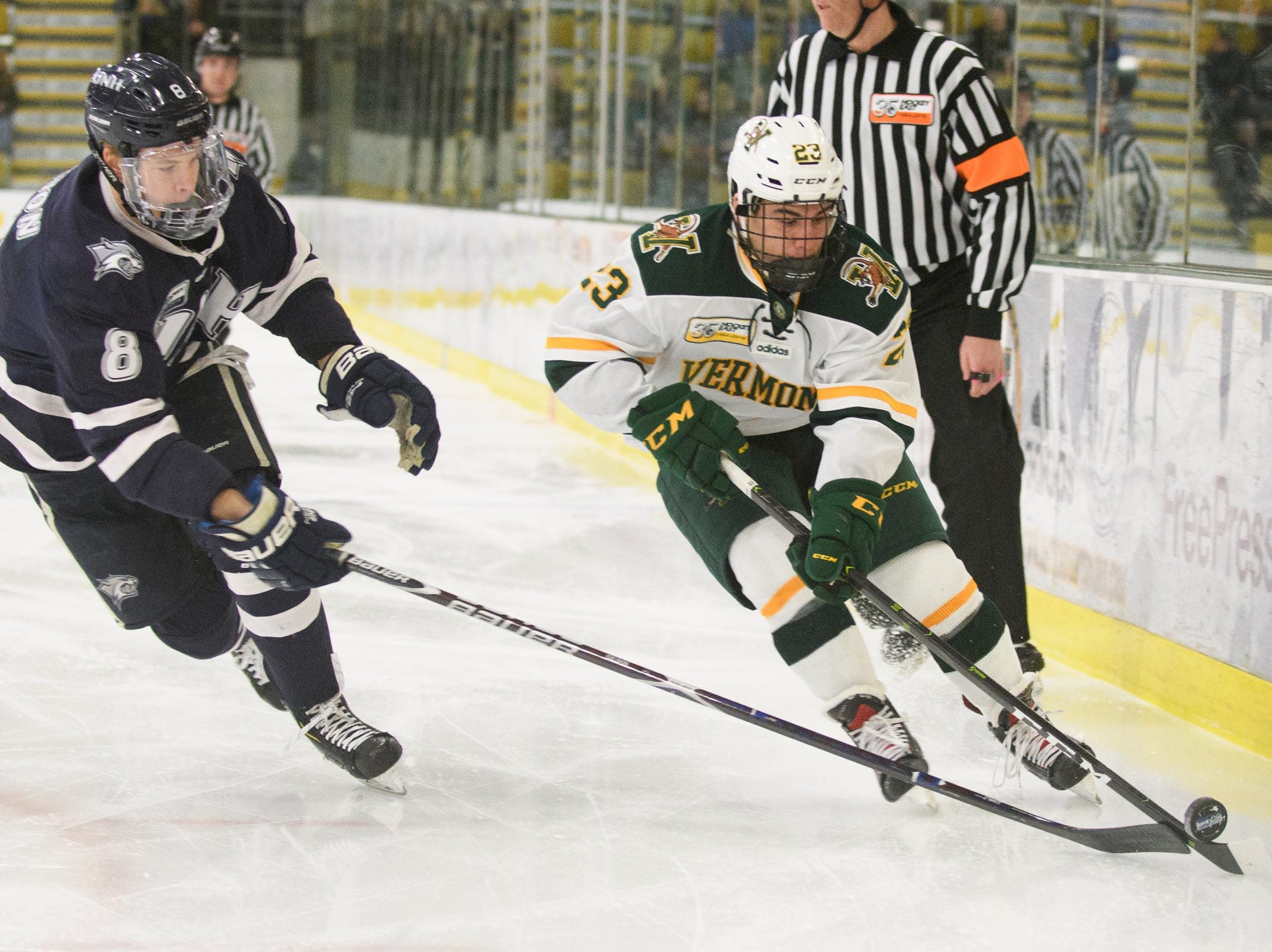 Vermont forward Max Kaufman (23) skates with the puck past New Hampshire's Max Gildon (8) during the men's hockey game between the New Hampshire Wildcats and the Vermont Catamounts at Gutterson Field House on Friday night February 8, 2019 in Burlington, Vermont.