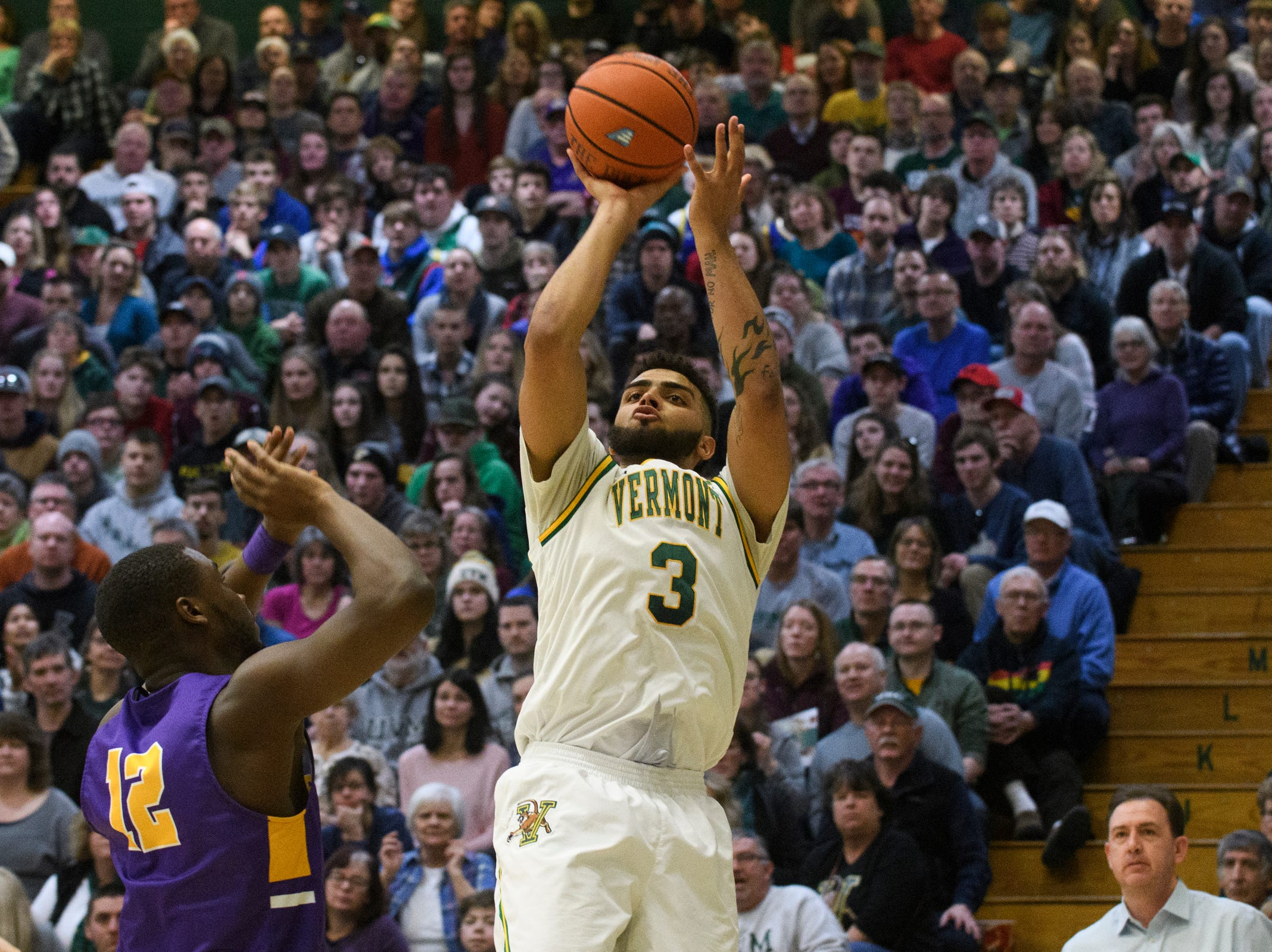 Vermont forward Anthony Lamb (3) shoots the ball over Albany's Devonte Campbell (12) during the men's basketball game between the Albany Great Danes and the Vermont Catamounts at Patrick Gym on Saturday February 9, 2019 in Burlington, Vermont.