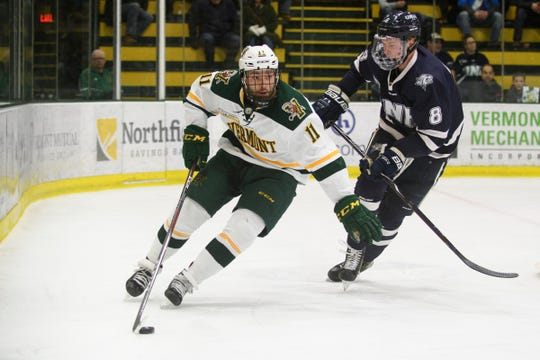Vermont forward Conor O'Neil (11) skates with the puck past New Hampshire's Max Gildon (8) during the men's hockey game between the New Hampshire Wildcats and the Vermont Catamounts at Gutterson Field House on Friday night February 8, 2019 in Burlington, Vermont.