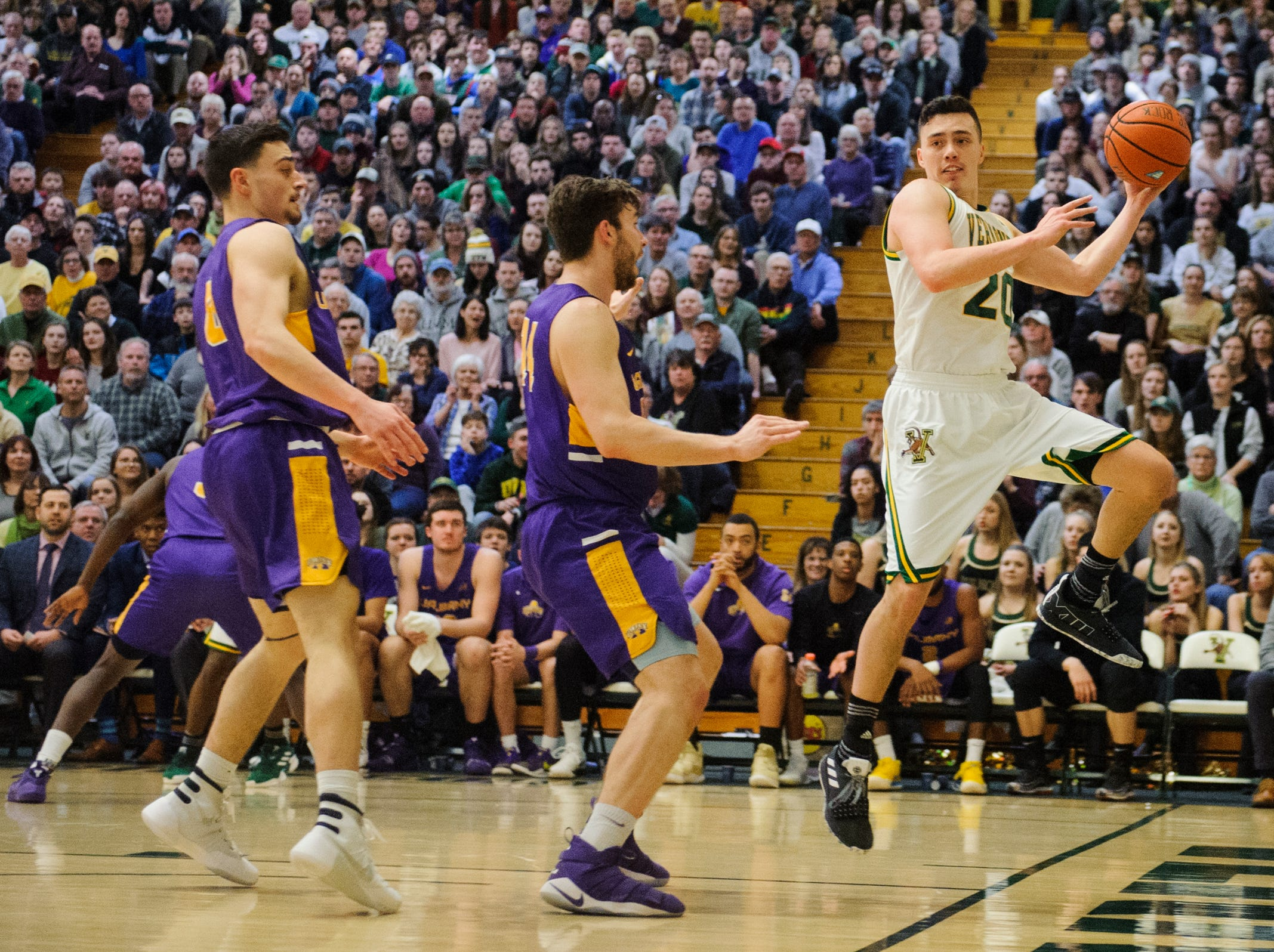 Vermont guard Ernie Duncan (20) leaps to save the ball from going out of bounds during the men's basketball game between the Albany Great Danes and the Vermont Catamounts at Patrick Gym on Saturday February 9, 2019 in Burlington, Vermont.