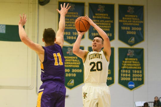 Vermont guard Ernie Duncan (20) shoots a three pointer over Albany's Cameron Healy (11) during the men's basketball game between the Albany Great Danes and the Vermont Catamounts at Patrick Gym on Saturday February 9, 2019 in Burlington, Vermont.