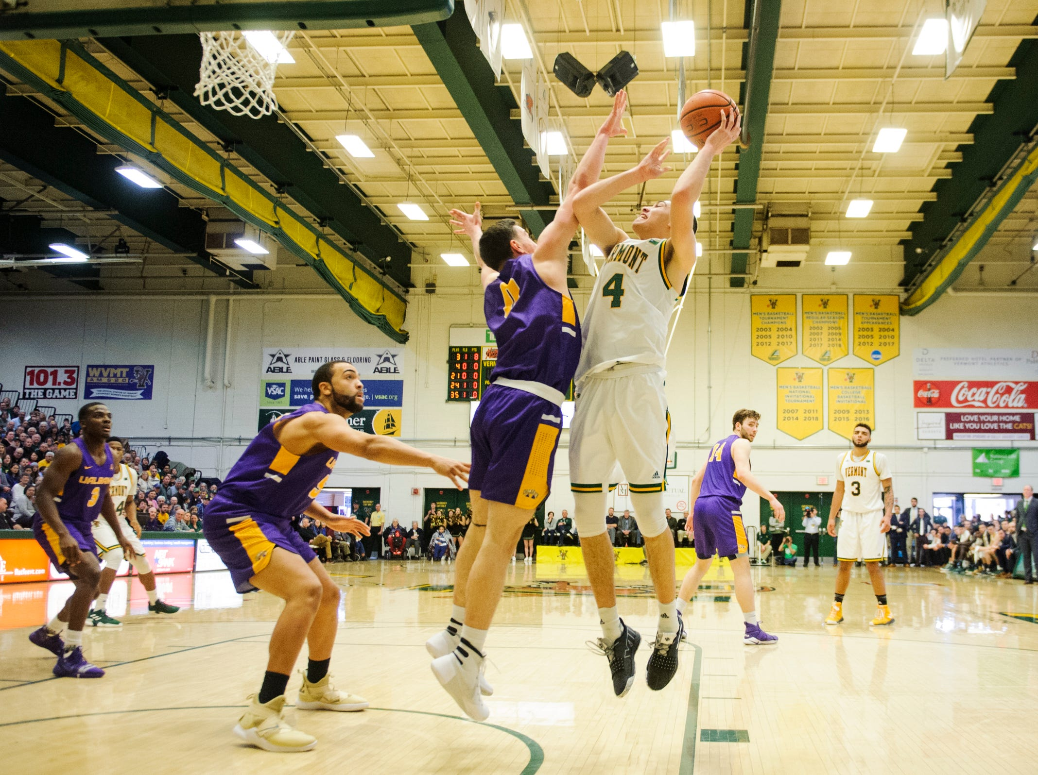 Vermont guard Robin Duncan (4) leaps for a lay up over Albany's Antonio Rizzuto (0) during the men's basketball game between the Albany Great Danes and the Vermont Catamounts at Patrick Gym on Saturday February 9, 2019 in Burlington, Vermont.