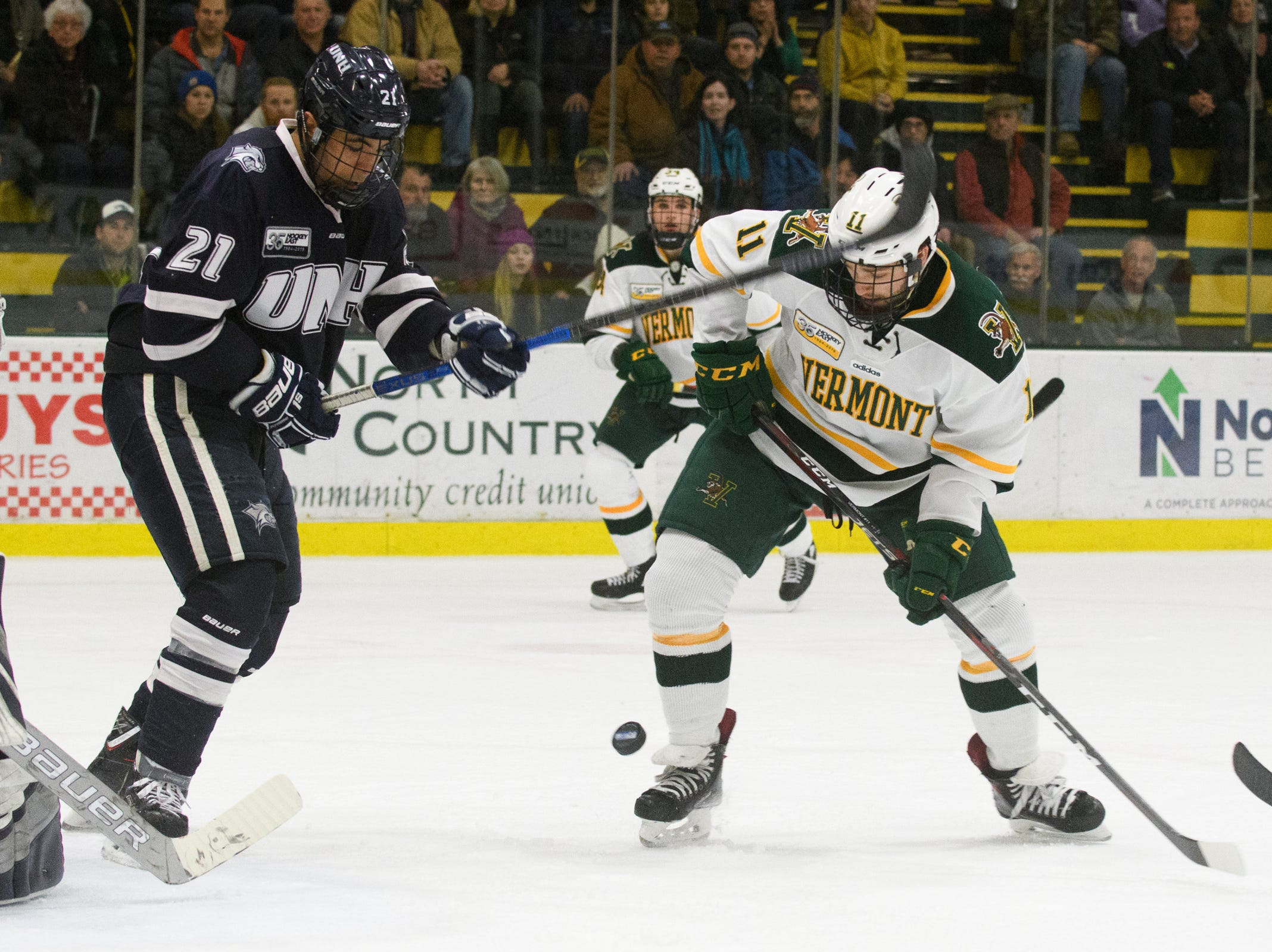Vermont forward Conor O'Neil (11) battles for the puck in front of the New Hampshire net during the men's hockey game between the New Hampshire Wildcats and the Vermont Catamounts at Gutterson Field House on Friday night February 8, 2019 in Burlington, Vermont.