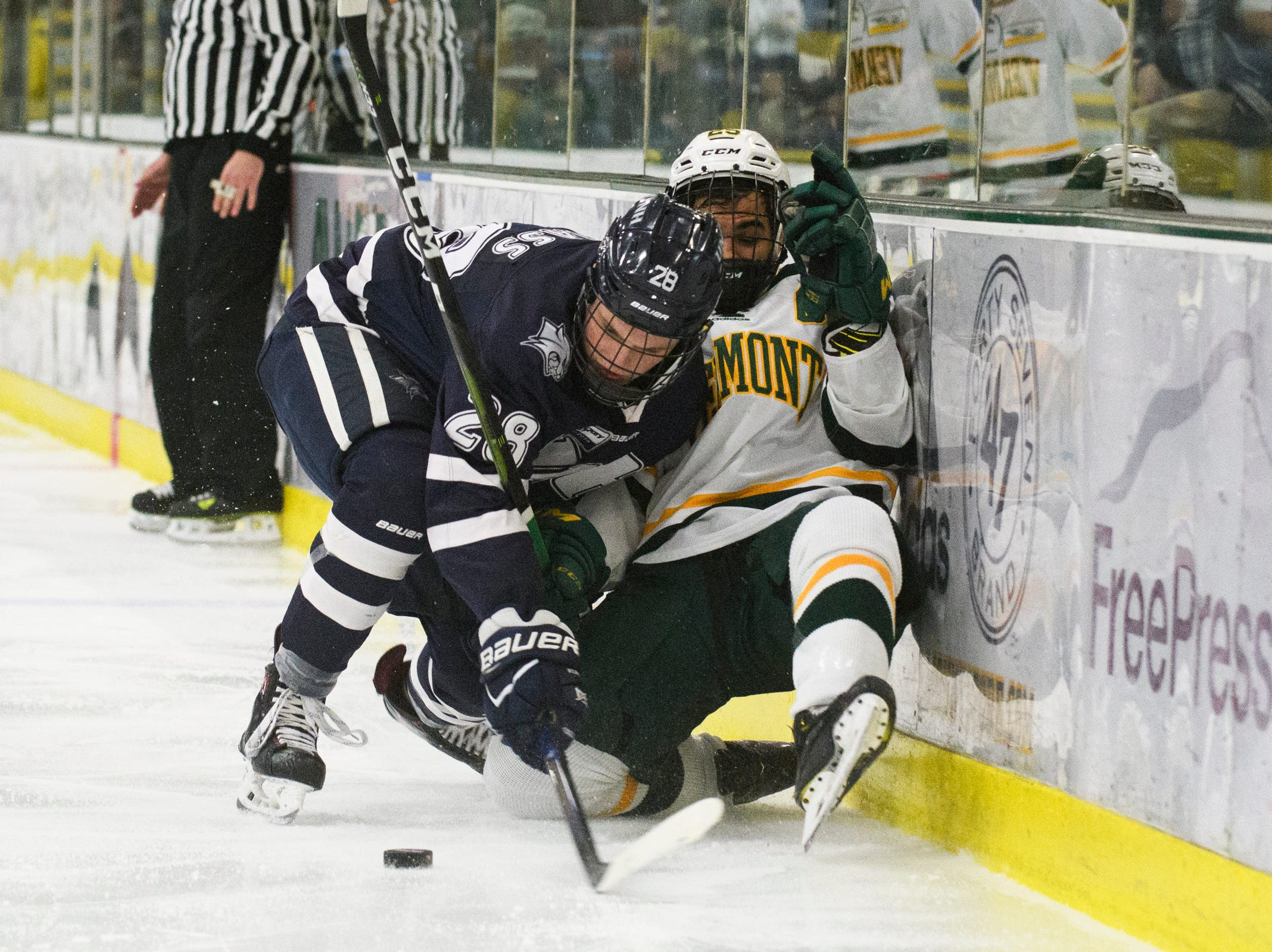 Vermont forward Matt Alvaro (25) and New Hampshire's Benton Maass (28) get tangled up as they battle for the puck during the men's hockey game between the New Hampshire Wildcats and the Vermont Catamounts at Gutterson Field House on Friday night February 8, 2019 in Burlington, Vermont.