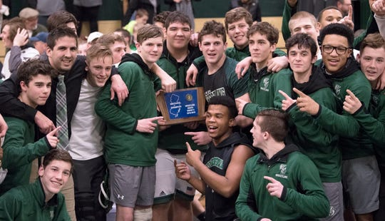 Members of the West Deptford High School wrestling team celebrate with their trophy after West Deptford defeated Haddonfield, 38-20, in the SJ Group 2 title meet held at West Deptford High School on Friday, February 8, 2019.