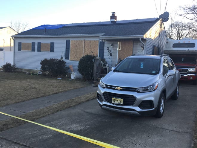 Two vehicles remain parked outside a Maple Shade home that was the scene of a fatal fire.