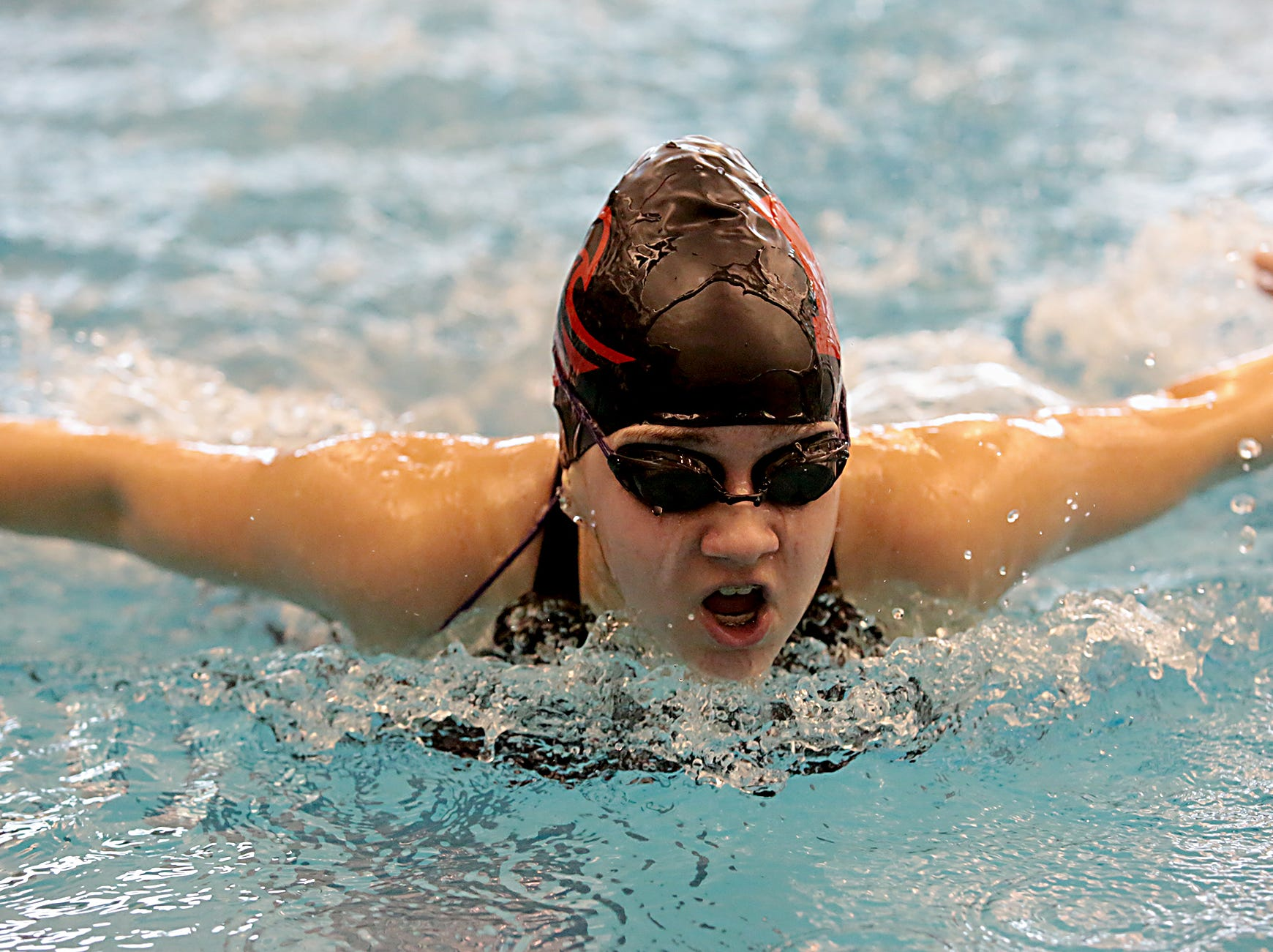 Lily Fleshour, from Milford, competes in the 100-yard butterfly during the Division I and II sectionals at Mason High School Saturday, Feb. 9, 2019.