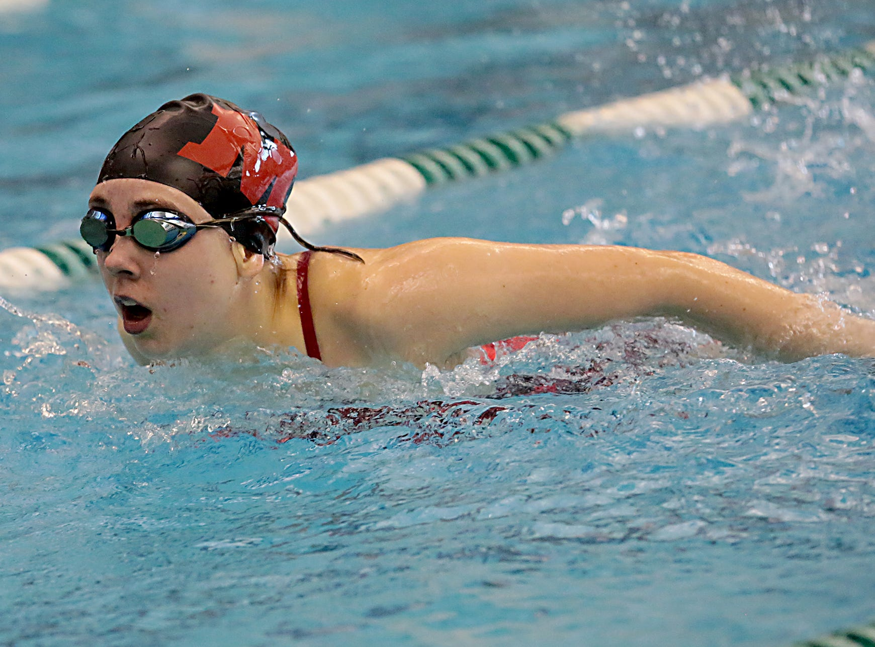 Samantha Chumley, from Milford, competes in the 100-yard butterfly during the Division I and II sectionals at Mason High School Saturday, Feb. 9, 2019.