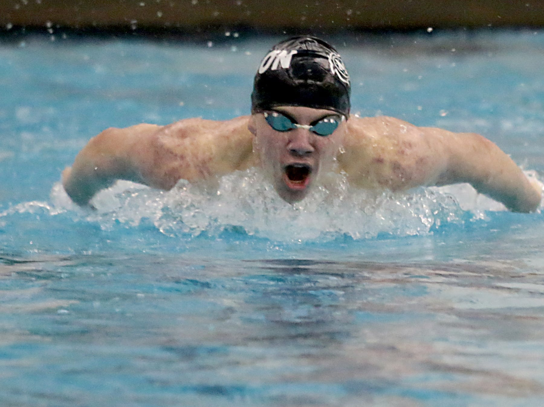 Carl Bloebaum, from Mason, competes in the 100-yard butterfly during the Division I and Division II sectionals at Mason High School in Mason Friday, Feb. 8, 2019.