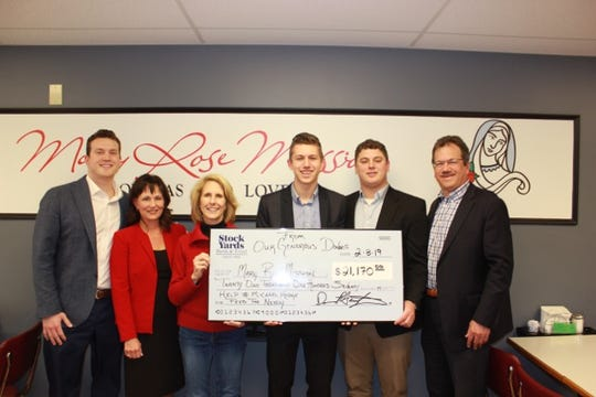 The Hodge family presented a check to Cindy Carris (third from left) and the Mary Rose Mission on Friday. The Hodges (pictured left to right) are: Andrew, Pamela, Michael, Alex and John.