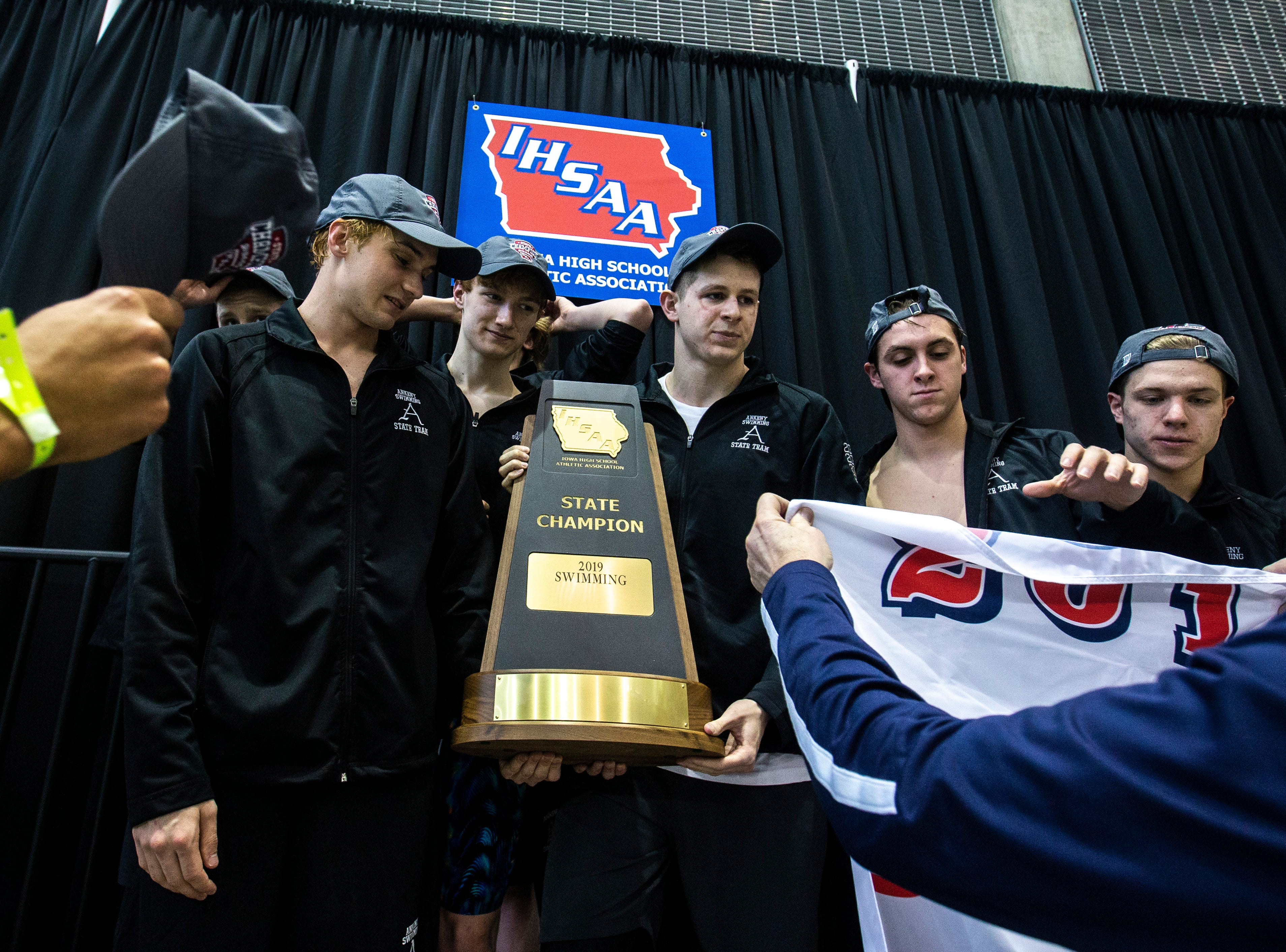 Ankeny swimming team holds their state trophy while receiving hats on the podium during the Iowa boys' state swimming regional championship meet on Saturday, Feb. 9, 2019 at Campus Recreation and Wellness Center on the University of Iowa campus in Iowa City, Iowa.