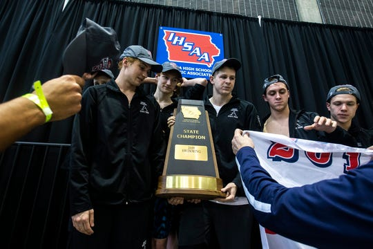 Members of the Ankeny swimming team hold their state trophy while receiving hats on the podium during the Iowa boys' state swimming regional championship meet on Saturday, Feb. 9, 2019, at Campus Recreation and Wellness Center on the University of Iowa campus in Iowa City, Iowa.