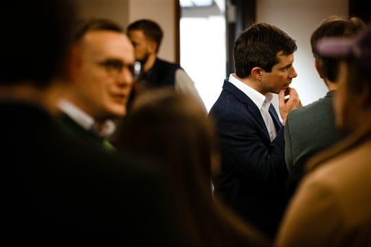 Pete Buttigieg, right, talks to attendees during a Feb. 8 campaign event at Vintage Cooperative in Ankeny.