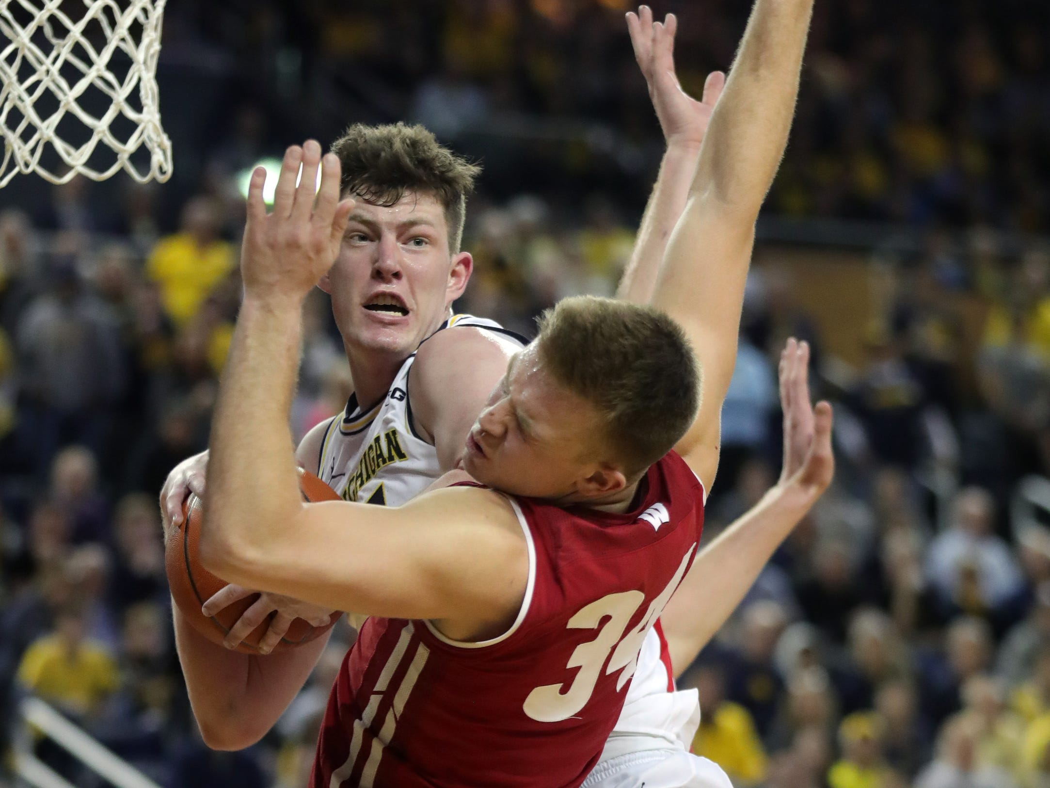 Michigan center Jon Teske rebounds against Wisconsin forward Nate Reuvers during the second half Saturday, Feb. 9, 2019 at the Crisler Center.