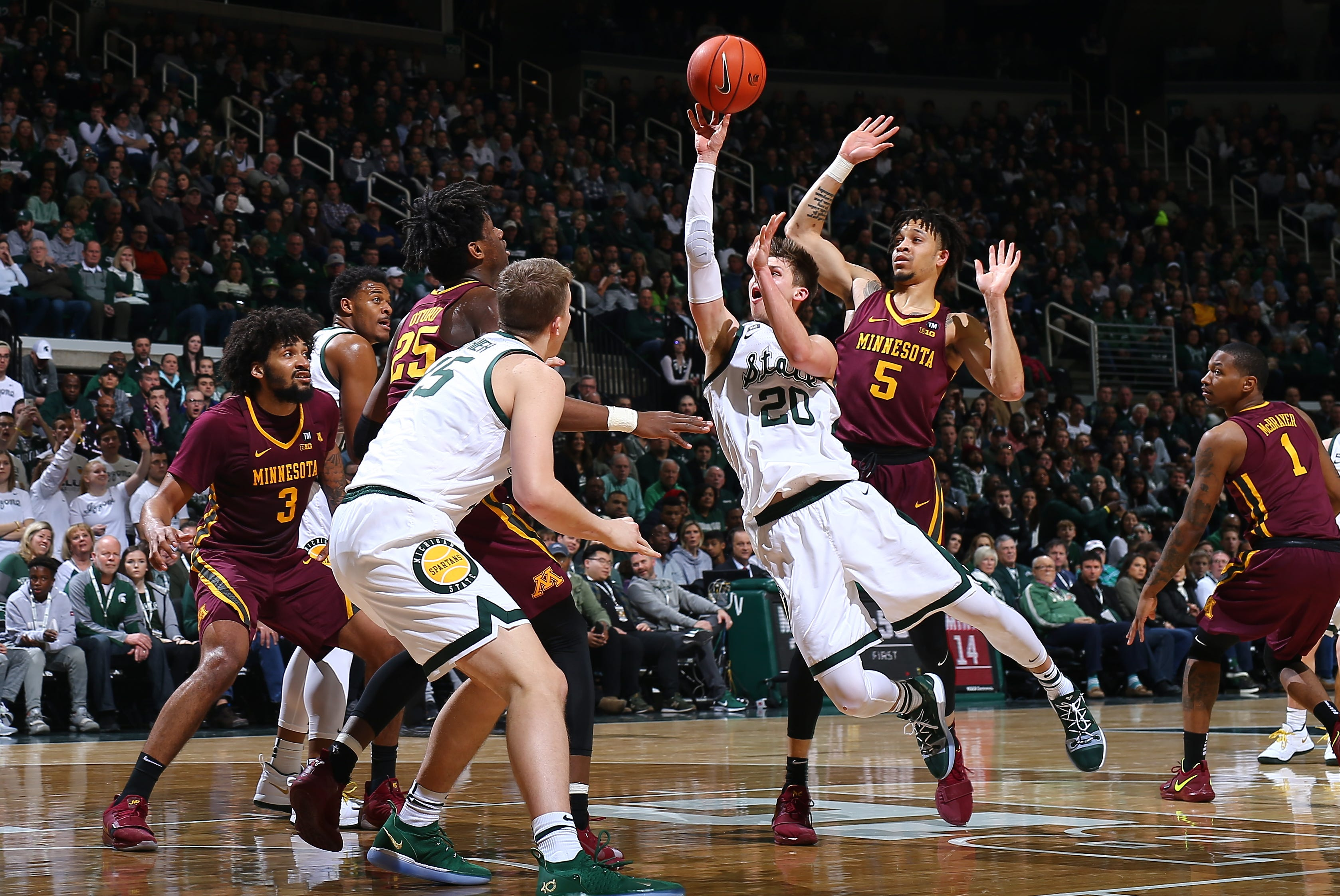 Michigan State's Matt McQuaid shoots the ball and draws a foul from Minnesota's Amir Coffey in the first half at Breslin Center on Saturday, Feb. 9, 2019, in East Lansing.