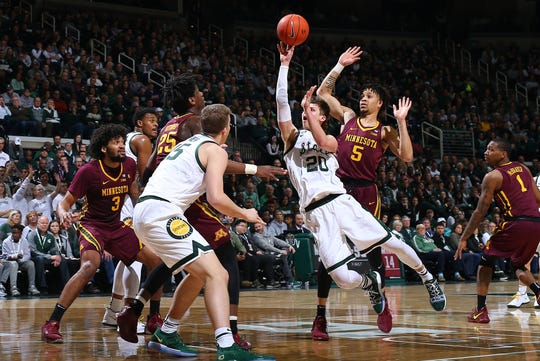 Michigan State's Matt McQuaid shoots and draws a foul from Minnesota's Amir Coffey in the first half at Breslin Center on Saturday, Feb. 9, 2019, in East Lansing.