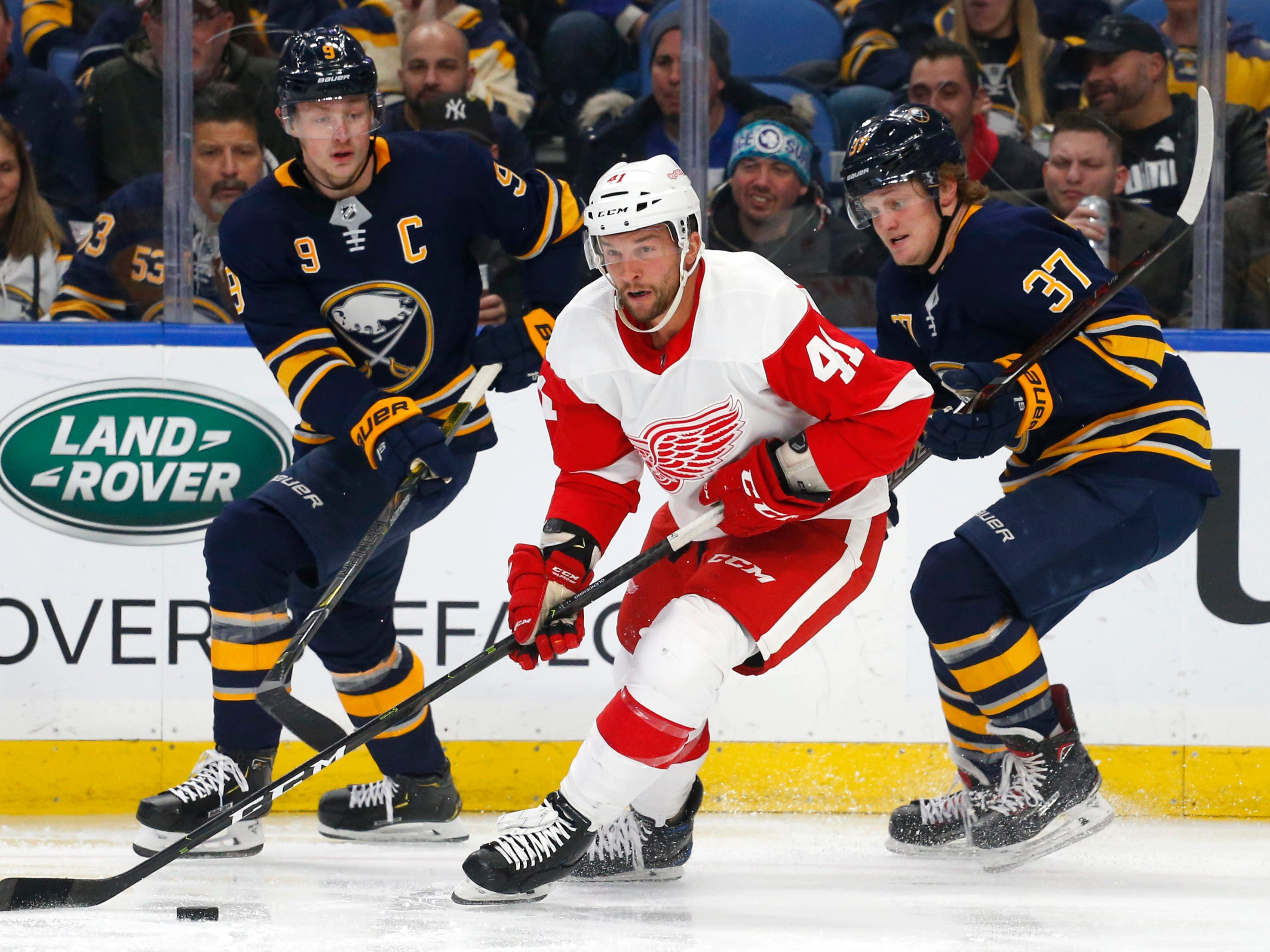 Red Wings forward Luke Glendening carries the puck past Sabres forwards Jack Eichel, left, and Casey Mittelstadt during the second period of the Wings' 3-1 loss on Saturday, Feb. 9, 2019, in Buffalo N.Y.
