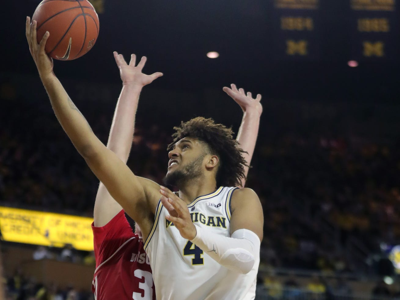 Michigan forward Isaiah Livers scores against Wisconsin forward Nate Reuvers during the first half Saturday, Feb. 9, 2019 at Crisler Center in Ann Arbor.