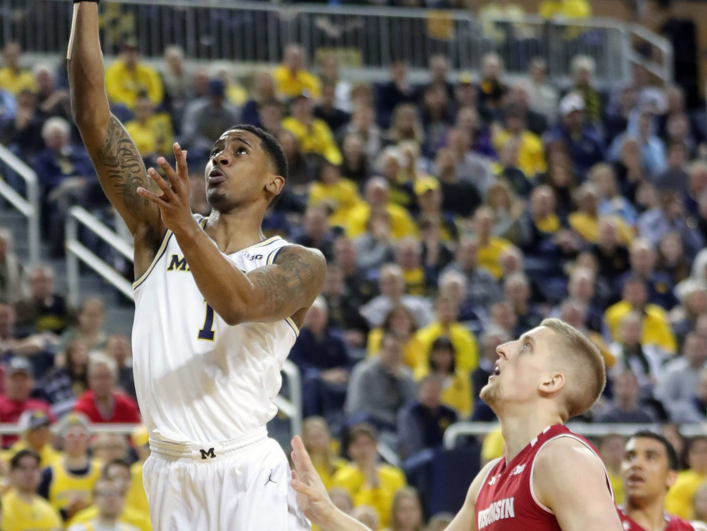 Michigan guard Charles Matthews scores against Wisconsin guard Brevin Pritzl during the second half Saturday, Feb. 9, 2019 at the Crisler Center.