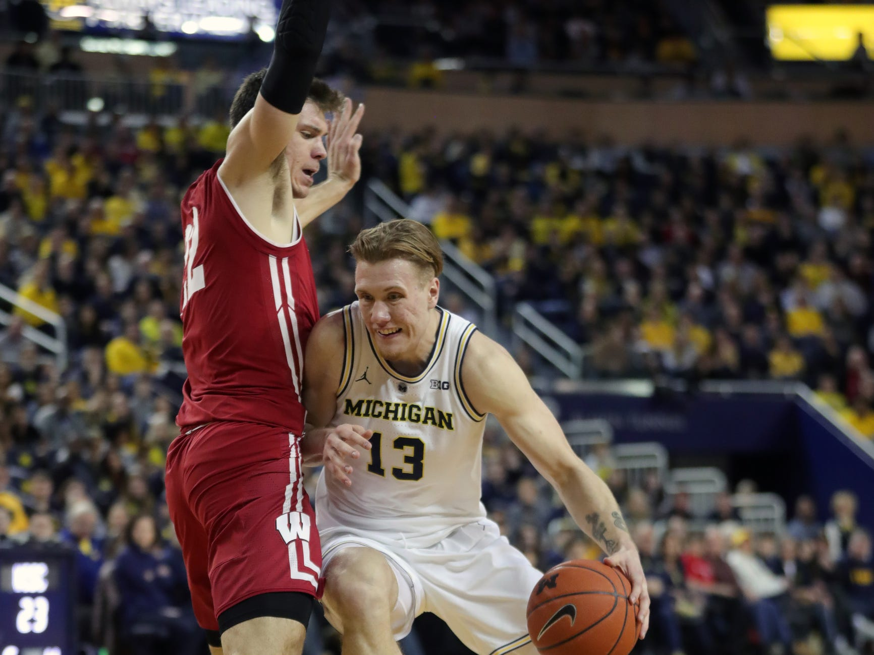 Michigan forward Ignas Brazdeikis drives against Wisconsin forward Ethan Happ during the first half Saturday, Feb. 9, 2019 at Crisler Center in Ann Arbor.