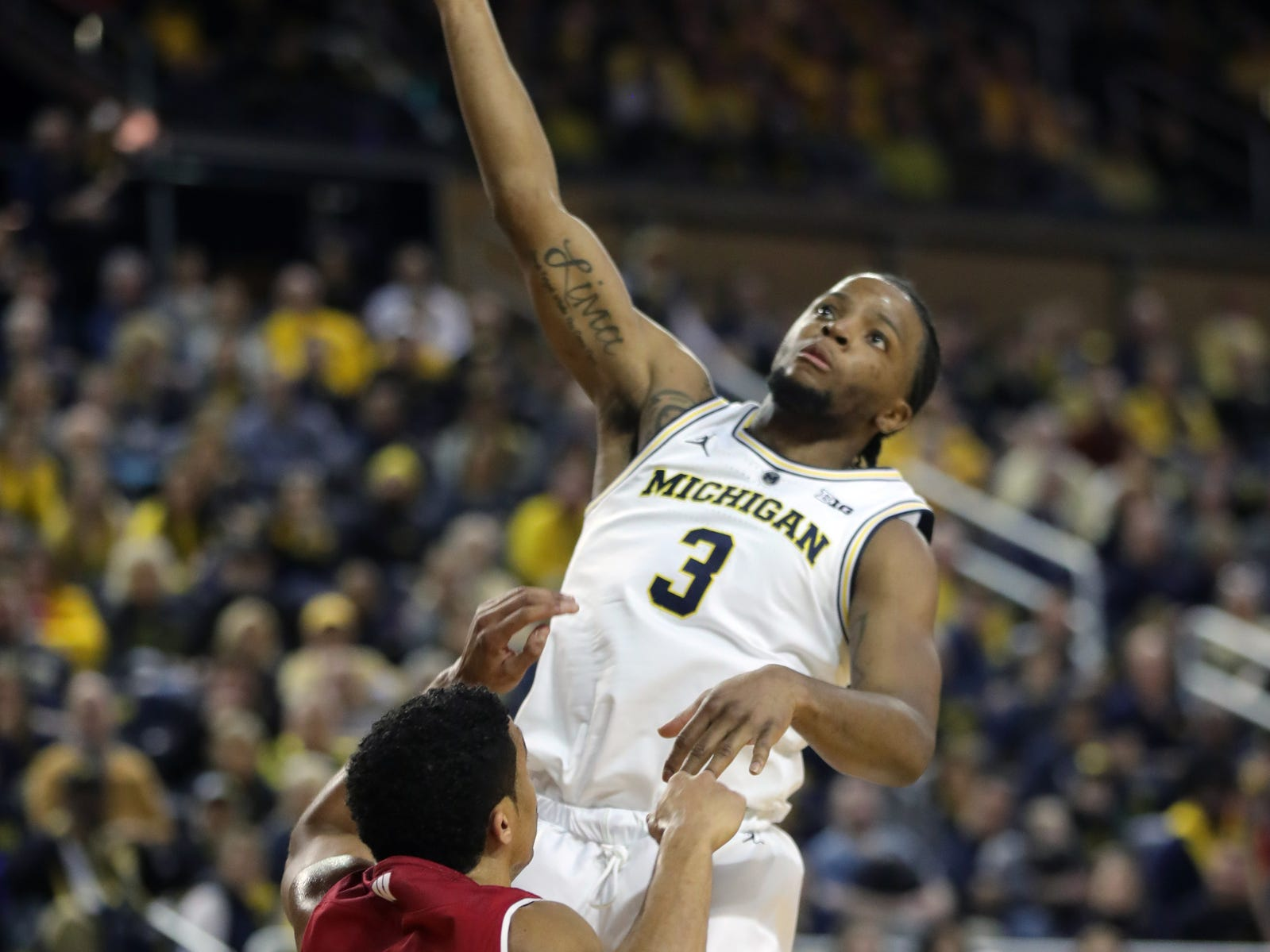 Michigan guard Zavier Simpson scores against Wisconsin guard D'Mitrik Trice during the first half Saturday, Feb. 9, 2019 at Crisler Center in Ann Arbor.