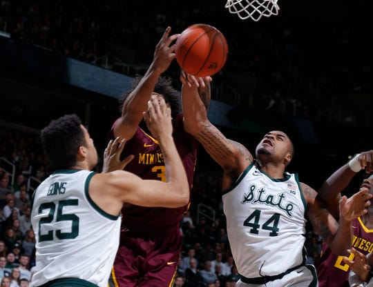 Nick Ward, right, Kenny Goins and Minnesota's Jordan Murphy, center, fight for a rebound during MSU's 79-55 win Feb. 9, 2019, in East Lansing.