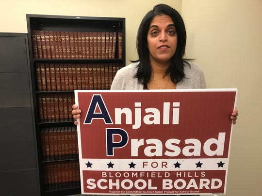 Attorney Anjali Prasad poses at her Royal Oak law offices, on Jan. 25, 2019, with one of her few yard signs that wasn't stolen, awaiting justice for the accused thief -- an elected Bloomfield Hills city commissioner.