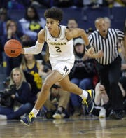Jordan Poole brings the ball up court against Wisconsin.