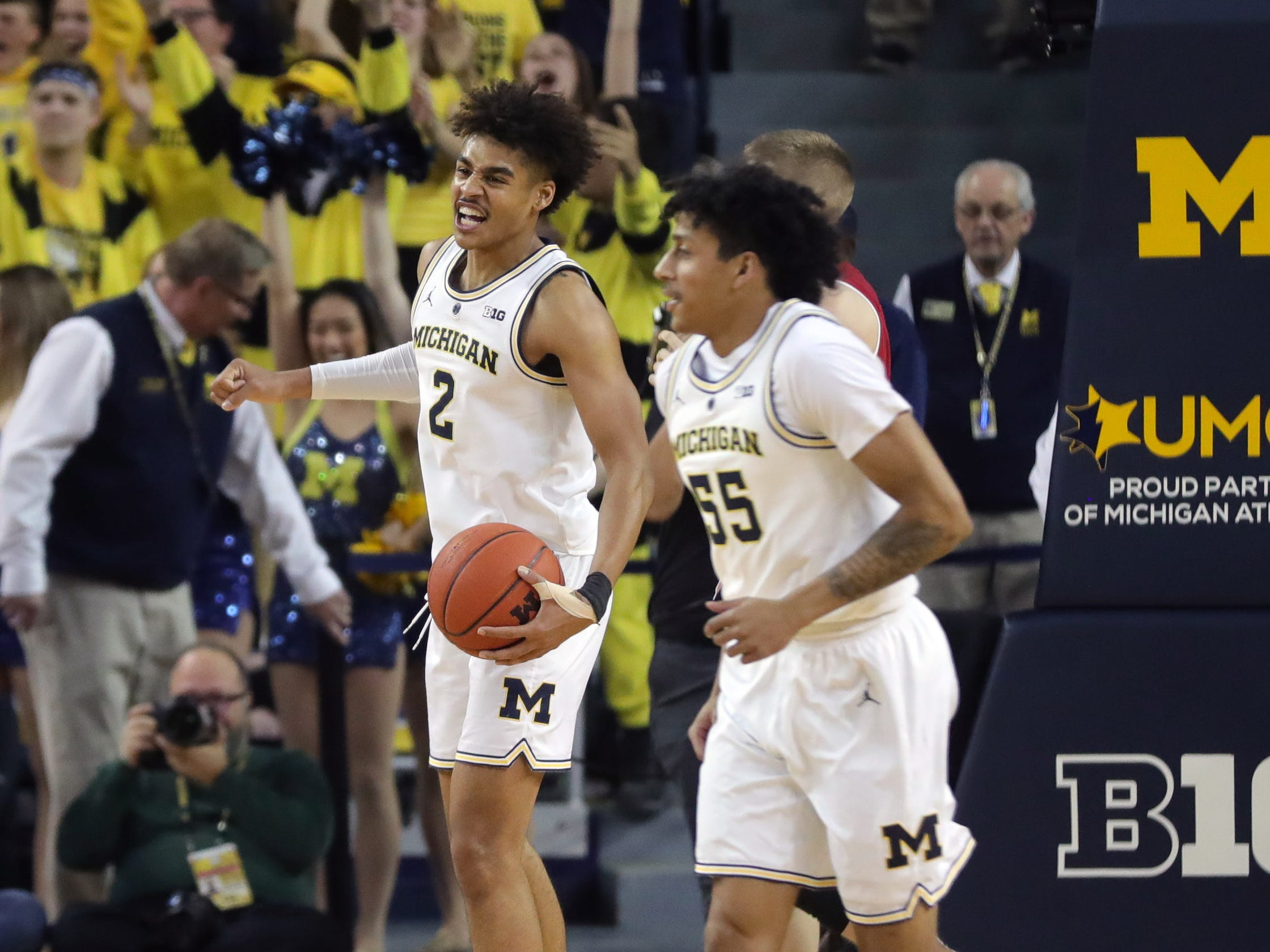 Michigan guards Jordan Poole and Eli Brooks celebrate the 61-52 win against Wisconsin, Saturday, Feb. 9, 2019 at the Crisler Center in Ann Arbor.