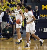 Jordan Poole and Eli Brooks celebrate the 61-52 win against Wisconsin.