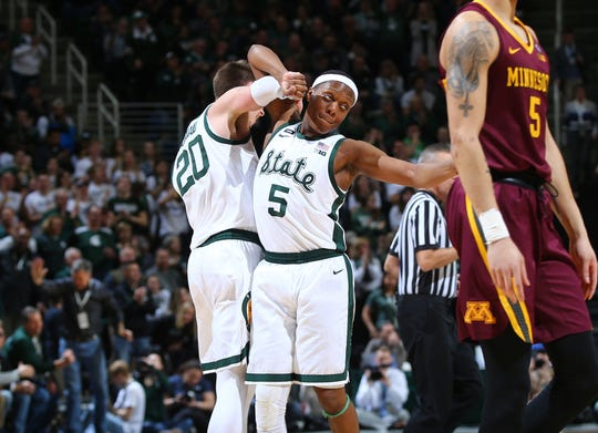 Matt McQuaid of the Michigan State Spartans celebrates his made basket with Cassius Winston in the second half.