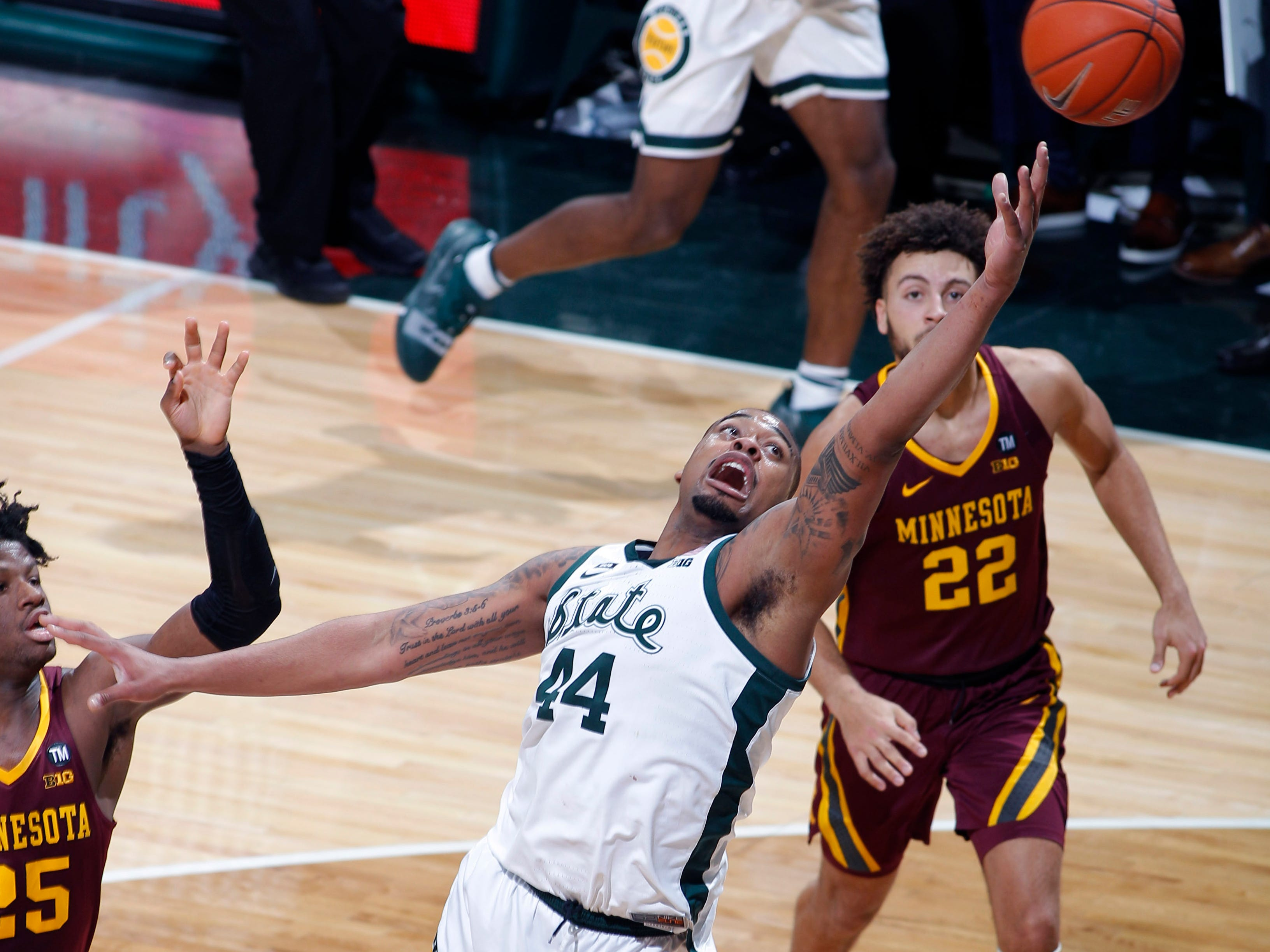 Michigan State's Nick Ward (44) reaches for the ball against Minnesota's Daniel Oturu, left, and Gabe Kalscheur (22) during the first half.