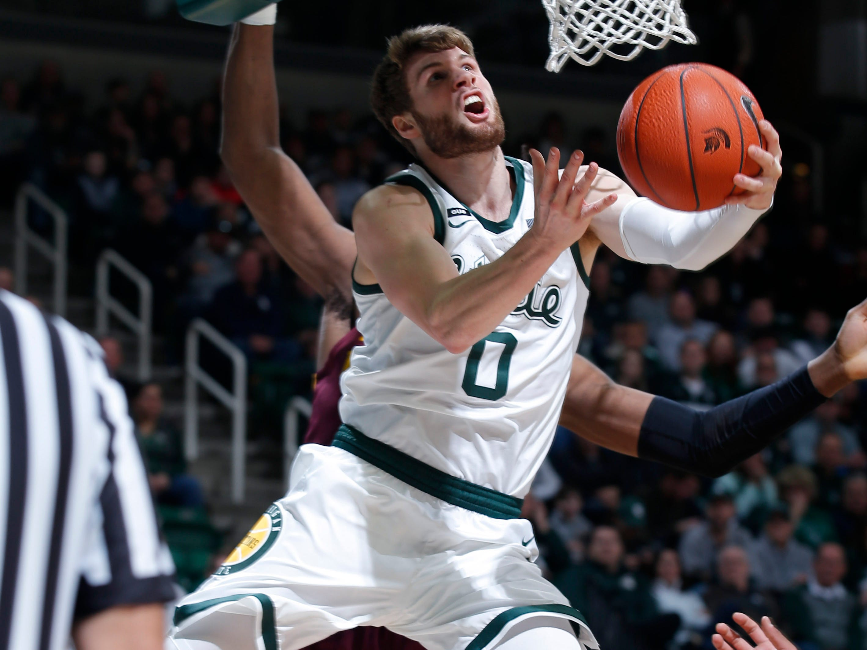 Michigan State's Kyle Ahrens (0) goes to the basket against Minnesota during the first half.