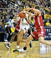 Wisconsin guard Khalil Iverson (21) and Wisconsin guard Brad Davison (34) defend a drive by Michigan guard Jordan Poole (2) in the first half Saturday at Crisler Center. Michigan would be the No. 6 seed overall and Michigan State No. 8 overall, according to the Men's Basketball Committee.