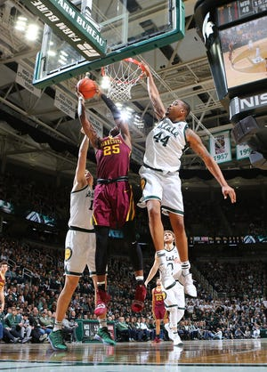 Daniel Oturuof the Minnesota Golden Gophers shoots the ball against Nick Ward of the Michigan State Spartans in the second half Saturday. Ward finished with 22 points in MSU's 79-55 win.