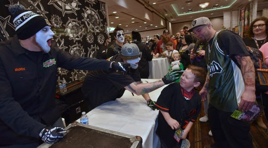 Detroit recording artists Jamie Madrox, left, and Monoxide, center, from Twiztid, tease Damian Mohawk, 7, and his father, Jake Mohawk, 29, both of Clinton Twp., during an autograph session.