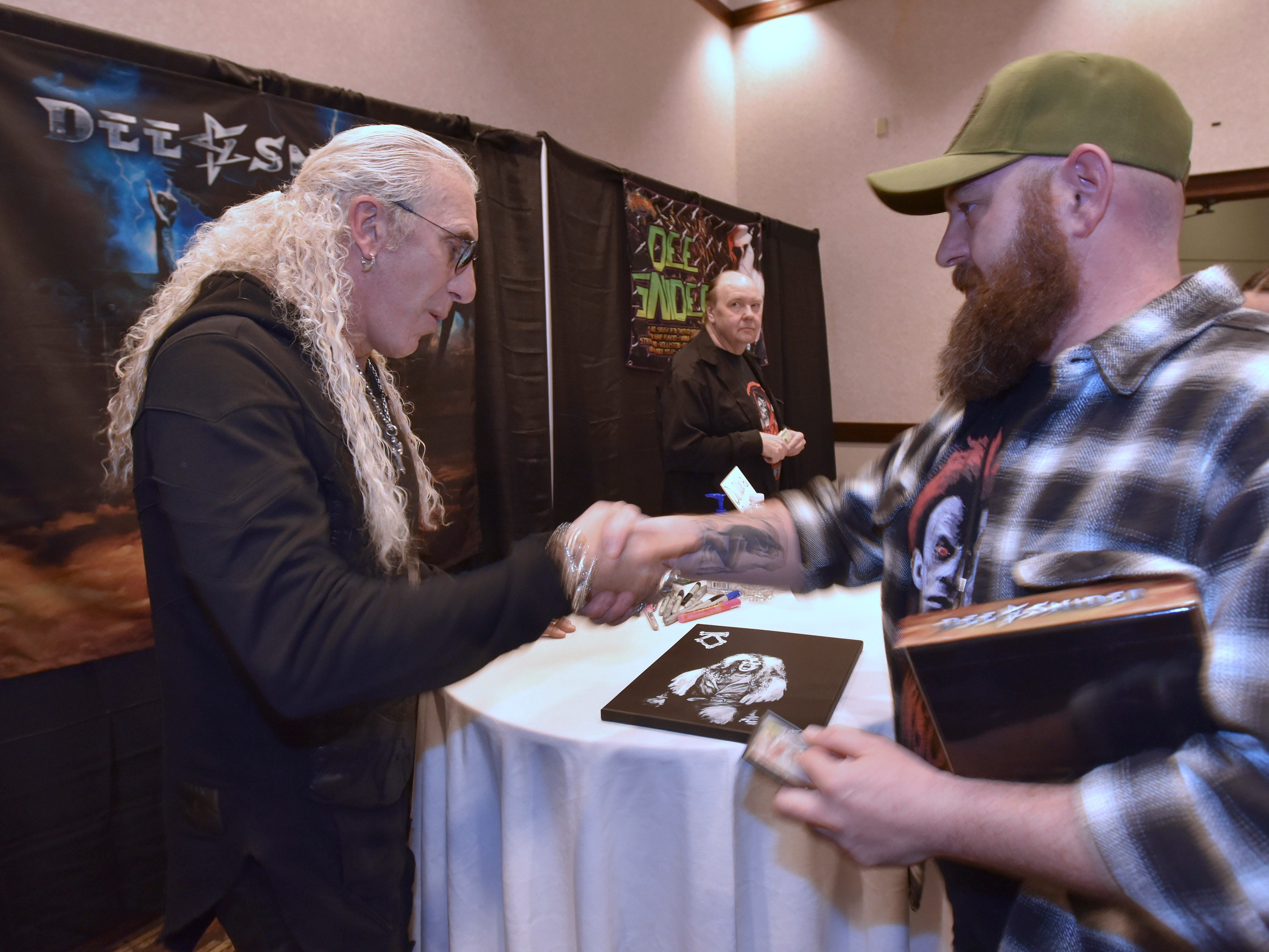 Twisted Sister frontman Dee Snider, left, shakes hands with fan Jason Zielke, right, 44, of Redford, before signing his autograph on a painting that Zielke made of Snider, Friday. Snider is promoting his new solo album, 'For the Love of Metal.'