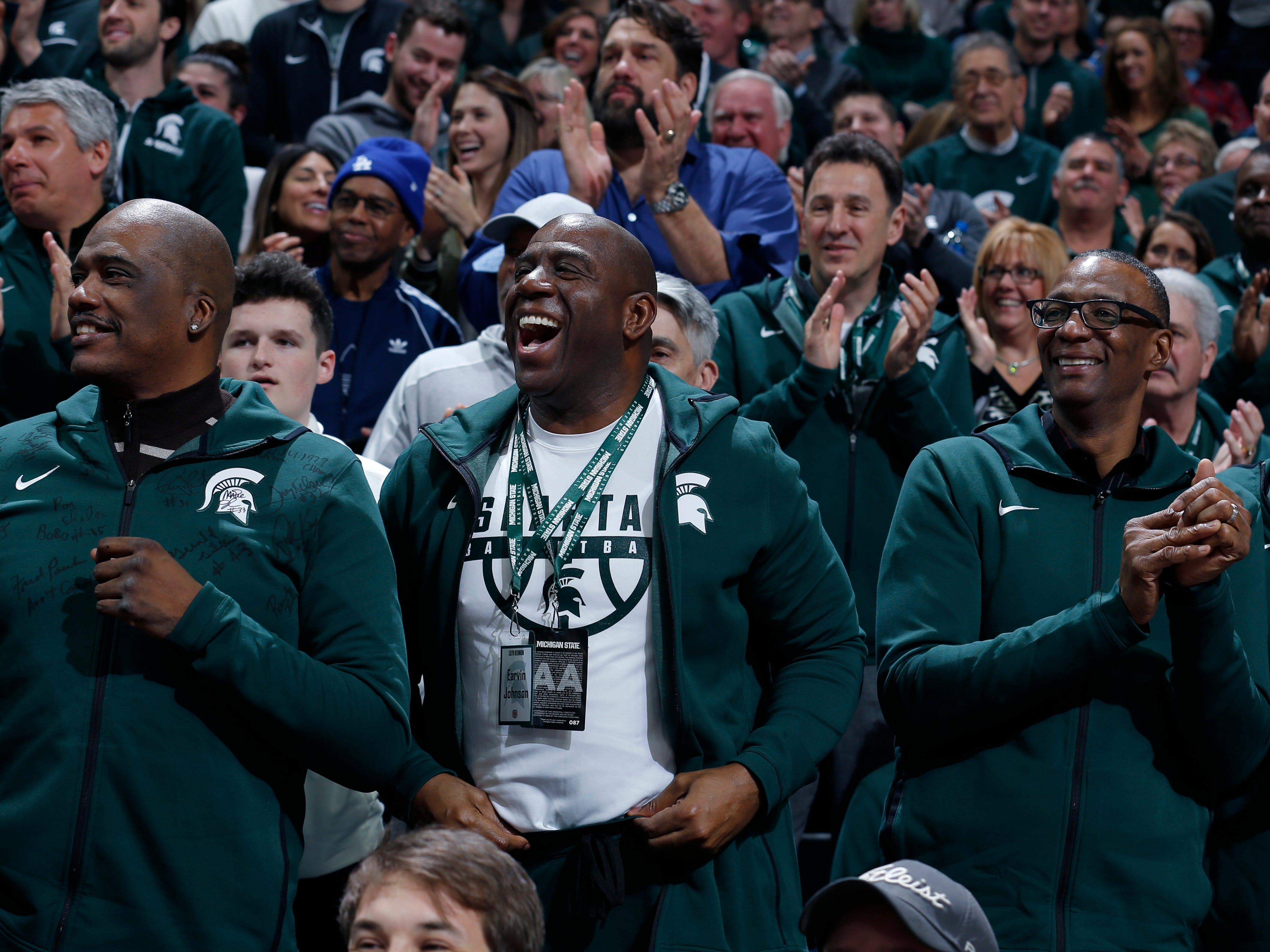 Former players on Michigan State's 1979 national championship team, including Magic Johnson, center, Jay Vincent, left, and Greg Kelser, right, react during the first half.