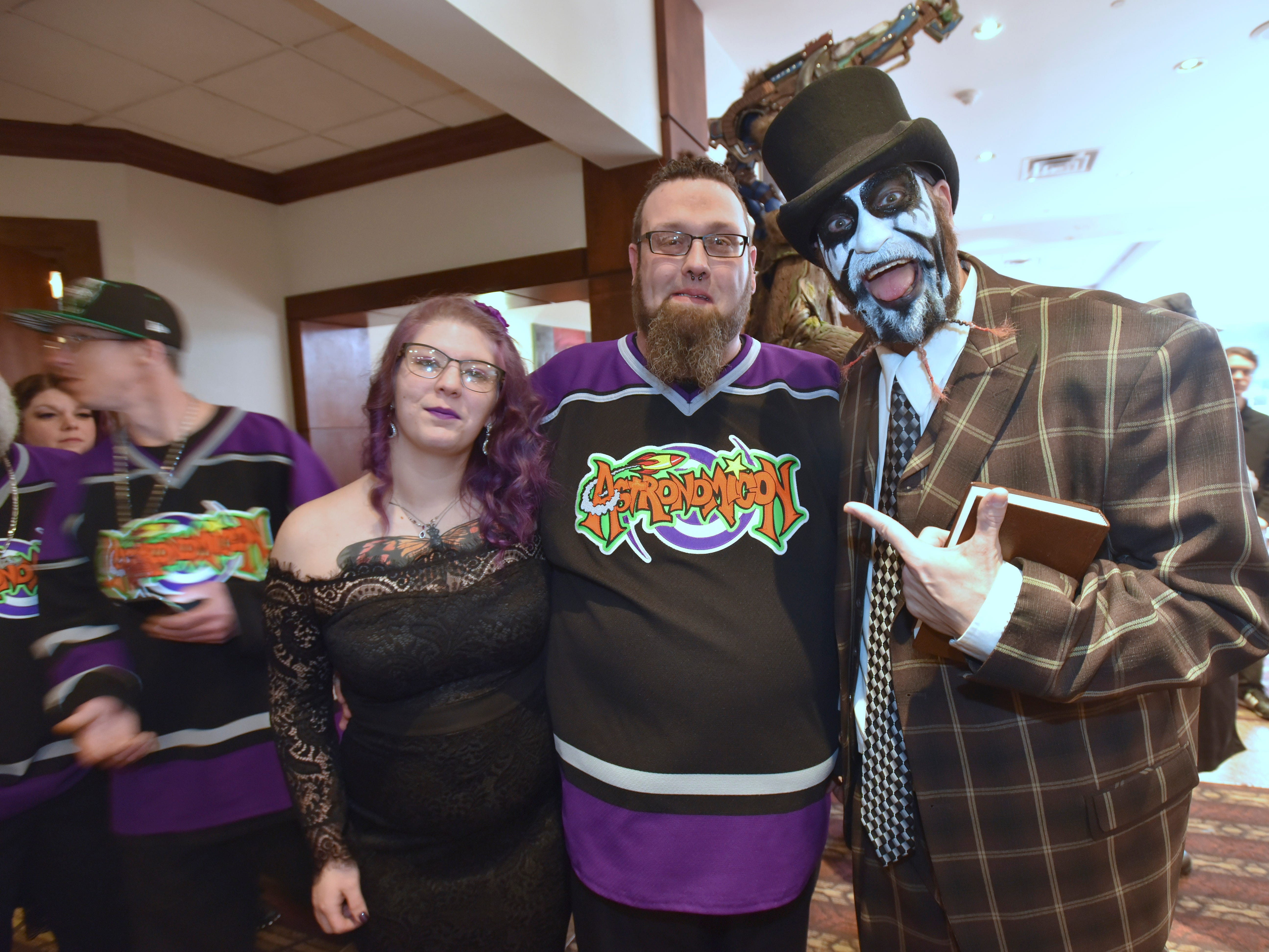 Amy Feero-Marr, left, 24, stands with her new husband, Bryce Marr, center, 32, both of Springfield, Illinois, stand with ordained minister 'Blaze Ya Dead Homie,' right, who is portrayed by Chris R, of Detroit, after he marries the couple at Astronomicon 2.